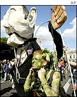 A protester in Berlin dressed as the earth pretends to be strangled by an effigy of George W Bush