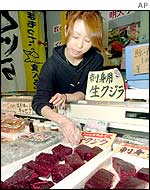 Japanese saleswoman arranges whale meat