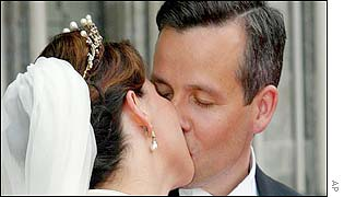 The newlyweds kiss outside the cathedral