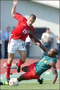 Joe Cole evades the Cameroon defender's challenge