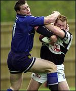 Brett Davey tussles with Steve Hanley for possession