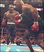 Evander Holyfield pours forward as Mike Tyson stumbles to the ropes