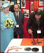 The Queen is shown an example of Chinese calligraphy reading Good Luck, Good Fortune, and Long Life, as she meets community groups in Glasgow