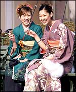 Young Japanese women aged 20 in traditional kimono dresses have a smoke after their coming of age ceremony