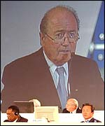 Sepp Blatter looms on a giant screen over Issa Hayatou