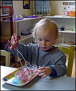 boy using tongs to move shaped objects
