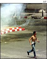 Protester runs to avoid tear gas in Tizi Ouzou