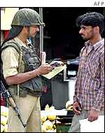 An Indian security guard checks a man's papers in Srinagar