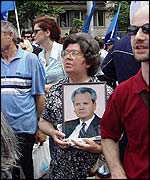 Milosevic supporter carries a portrait of him at a Belgrade rally