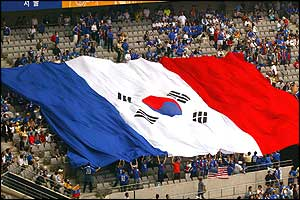 In the spirit of togetherness fans display a French flag adorned with the South Korean emblem