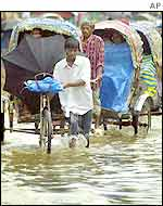 Dhaka rickshaw pullers wade through rain water