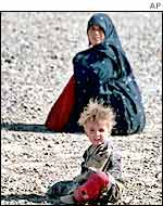 Mother and child waiting in a barren camp near the Iranian border