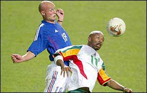 Diouf evades Leboeuf's challenge during his team's 1-0 win over France