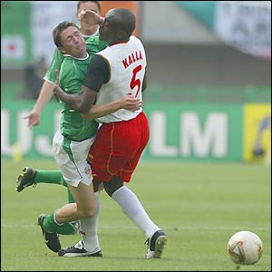 Robbie Keane is blocked by Cameroon's Raymond Kalla