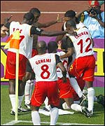The Cameroon player's surround goalscorer Patrick Mboma after he gave his side the lead