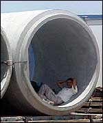 Man shelters from sun in concrete pipe