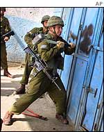 An Israeli soldier uses a sledge hammer to smash a door in Balata refugee camp, Nablus