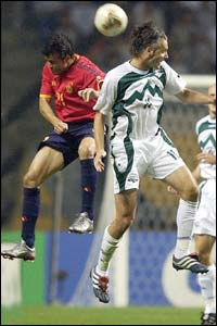 Spain midfielder Luis Enrique jumps with Slovenia's Miran Pavlin