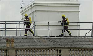 Firemen scour the roof top near the blaze