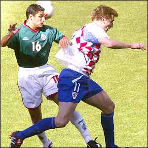 Mexican defender Salvador Carmona (L) heads off the ball in front of Croatian forward Alen Boksic
