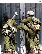 Israeli soldiers kick in a door