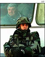 UN soldier guarding a bus carrying Serb refugees