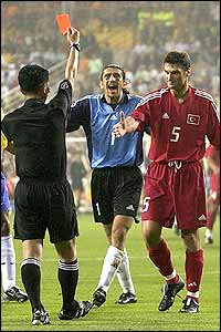The first of two red cards for Turkey is shown to ALpay Ozalan