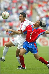 Wu Chengying of China competes for the ball with Gilberto Martinez of Costa Rica