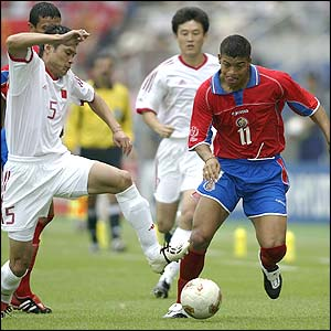 Costa Rica's Ronald Gomez runs past Fan Zhiyi of China in their opening Group C battle
