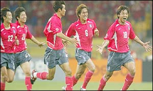 Hwang Sun-hong is chased by celebrating team-mates