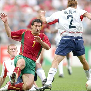 Portugal's Luis Figo is tackled by USA's John O Brien as his team-mate Frankie Hejduk steals the ball