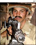 A Pakistani soldier with a machine gun in a bunker near the Kashmir border