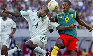Saudi defender Abdullah Sulaiman Zubromawi (L) heads off the ball in front of Cameroon forward Samuel Etoo