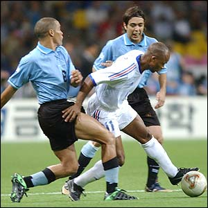 France forward Sylvain Wiltord flanked by Uruguay's Dario Rodriguez and Alvaro Recoba