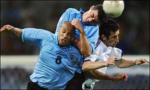 Uruguay's Alejandro Lembo and Gustavo Varela tussle with Johan Micoud of France  (right)