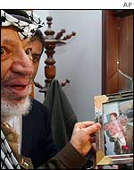 Yasser Arafat with photo of himself and daughter