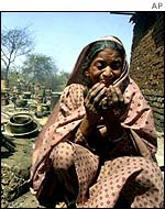 Muslim woman prays outside her burned home in Ahmedabad