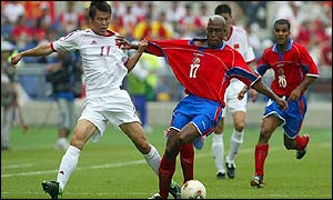 Yu Genwei of China pulls the shirt of Hernan Medford