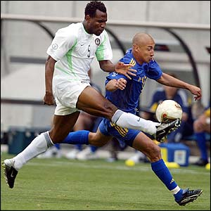Nigeria's Isaac Okoronkwo clears the ball away from Sweden's Henrik Larsson
