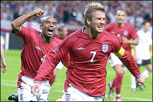 Substitute Trevor Sinclair chases goalscorer David Beckham to begin the celebrations