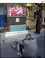 A homeless man watches the game on a shop TV