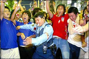 A Japanese police officer grimaces as he tries to hold back frantic England supporters