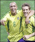 Roberto Carlos celebrates with Juninho after setting Brazil on their way