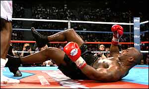 Mike Tyson sprawls on the canvas in the fourth bur Lewis was docked a point for a push