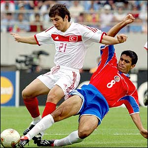 Costa Rica's Mauricio Solis vies for the ball with Turkey's Emre Belozoglu