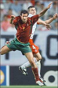 Portugal's Luis Figo is challenged in the air by Michal Zewlakow