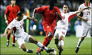 Belgium's Mbo Mpenza is tackled by Raouf Bouzaine and Slim Ben Achour