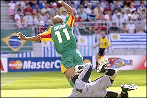 Uruguay's goalkeeper Fabian Carini fouls Senegal's El Hadji Diouf in the penalty area