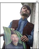 Supporter of interim Afghan leader Hamid Karzai putting up a poster