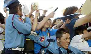 Japanese fans of the Italy team scream for autographs in Sendai as police try to contain them